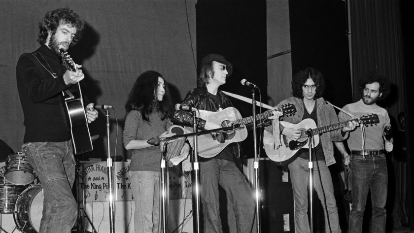 John Lennon and Yoko with Jerry Rubin(far right) playing percussion onstage at the Apollo Theater