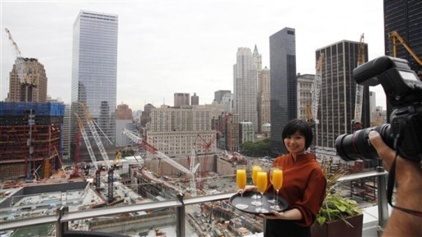 Nora Bourabah, a waitress with the View of the World Terrace Club, poses for photographers at the newly-opened World Center Hotel, Wednesday, June 9, 2010, in New York. The rising tower of One World Trade Center is at left. The boutique hotel has 169 rooms, most with views of the World Trade Center or Lower Manhattan. (AP Photo/Mark Lennihan)