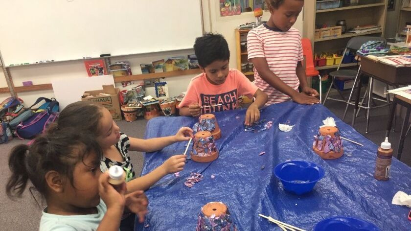 Children decorate flower pots for an art class at CREER, a program created 15 years ago to support education for kids from low-income familers in San Juan Capistrano.