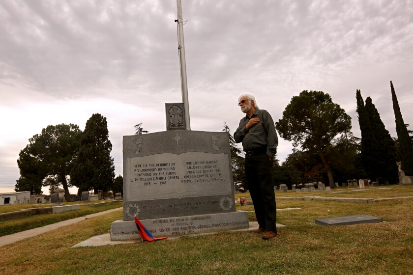 A man stands with his right hand over his heart next to a large headstone in a cemetery