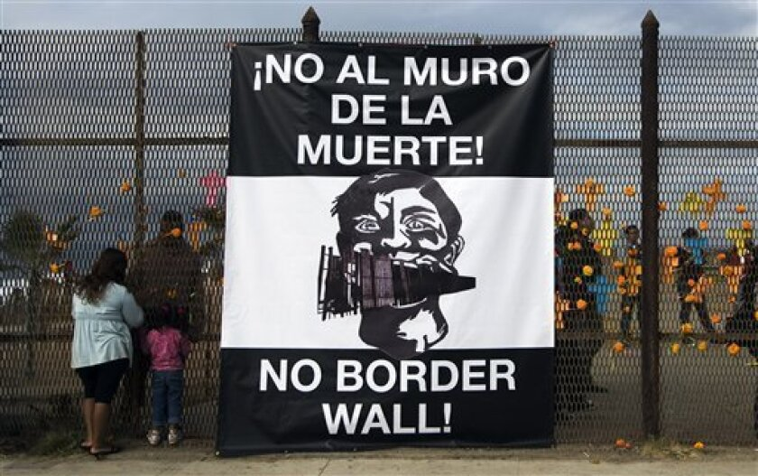 A sign hung by the Raza Rights Coalition hangs on the Mexican side of the U.S.-Mexico border fence in Friendship Park in Tijuana, Mexico, Sunday, Nov. 2, 2008. The U.S. Border Patrol will close the park on a bluff overlooking the Pacific Ocean to make way for a triple fence, people who were informe