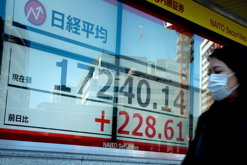 A woman walks past a display board March 17 at the Tokyo Stock Exchange.
