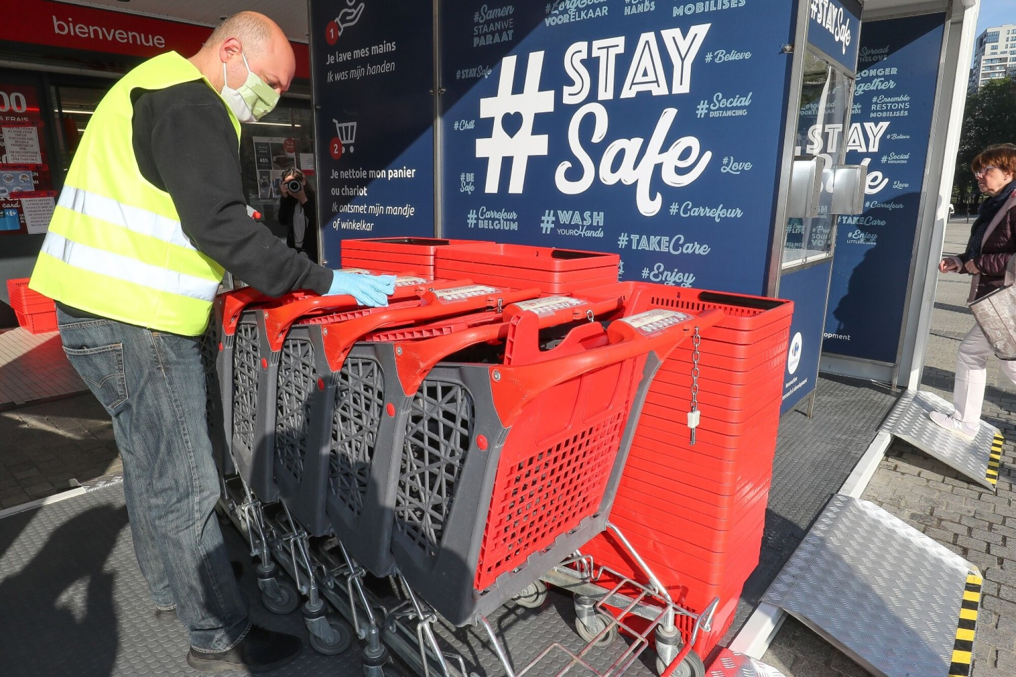 "A man arranges shopping carts at a ""disinfectant unit"" at a  Brussels supermarket Friday."