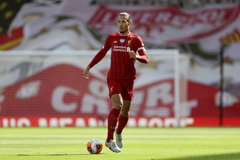 FILE - In this Sunday, July 5, 2020 file photo, Liverpool's Virgil van Dijk runs with the ball during theie English Premier League soccer match against Aston Villa at Anfield Stadium in Liverpool, England. Liverpool ended a 30-year wait for a league title in style last season as Jurgen Klopp's men lost only three times en route to lifting the trophy last month - retaining the crown is often a more difficult proposition, however, and the Reds will have to remain at their best if they are to do so. (Carl Recine/Pool via AP, file)