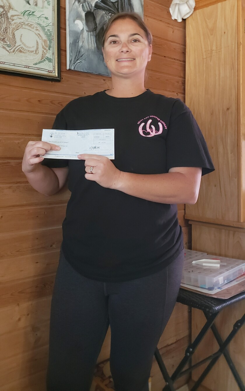 Heart and Hooves Therapy President/Founder Melissa Sargent displays a $1,000 grant check from Ramona Community Foundation.