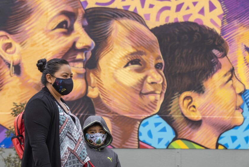 A mother and son, wearing masks, stand in front of a mural