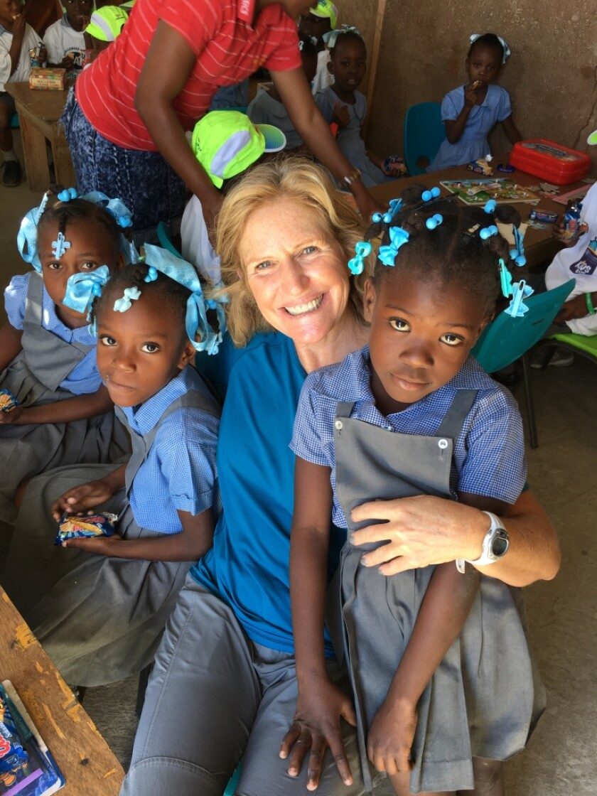 Stephanie Hoffman, owner of La Jolla Shores Physical Therapy, poses with students of Institut Edeline, a K-7 school in Haiti.