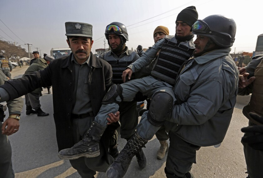 Afghan police carry an injured colleague after a clash with protesters in Kabul.