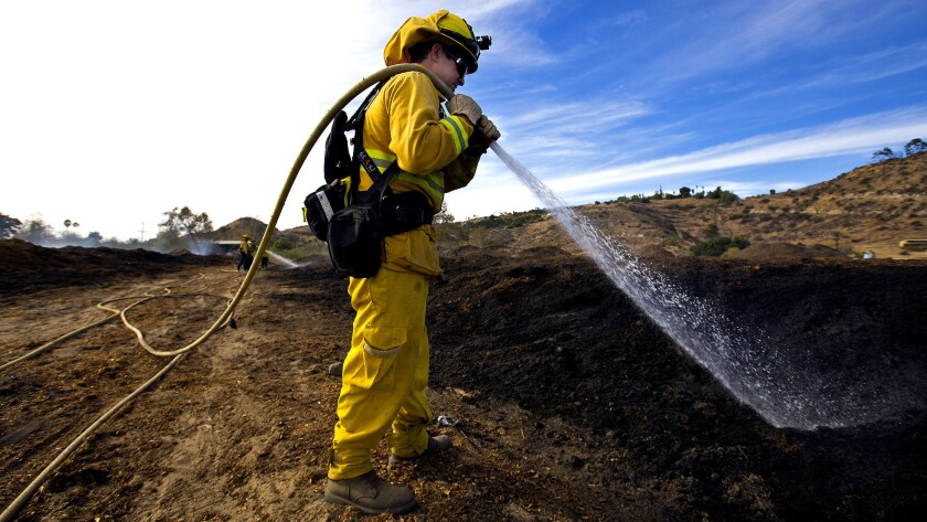 Aaron Wittmers of the Vacaville Fire Protection District douses a smoldering field of compost Saturday in Bonsall, Calif.
