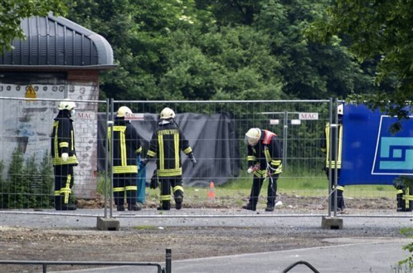 Firefighters inspect the area where a bomb exploded in Goettingen, Germany late Tuesday, on Wednesday June 2, 2010. Police say three experts working to defuse a bomb dating back to World War II were killed when the device exploded, injuring six others. Goettingen police say residents from around the area where the bomb was found were still being evacuated when it detonated late Tuesday. (AP Photo/ddp/Eckehard Schulz)