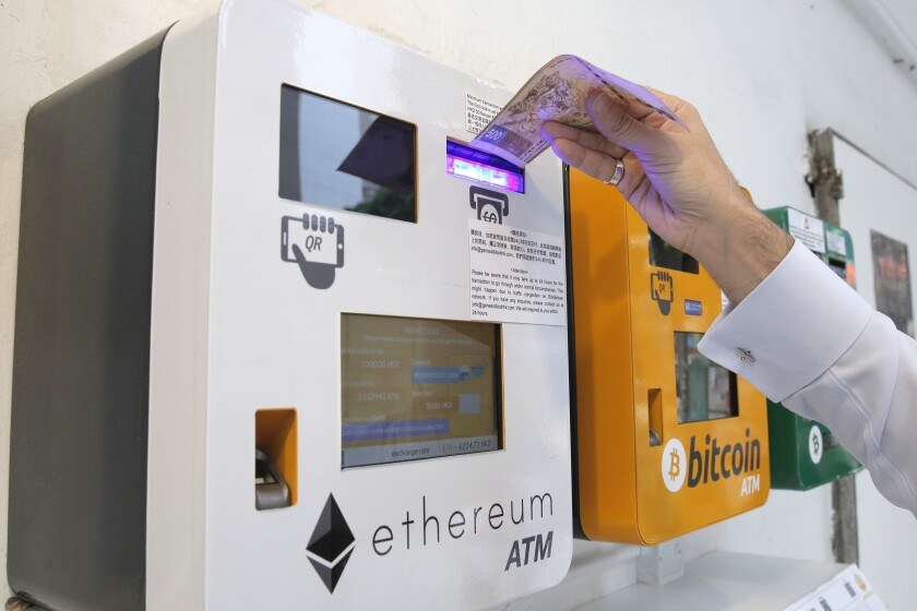 A man uses an Ethereum ATM next to a bitcoin ATM FILE