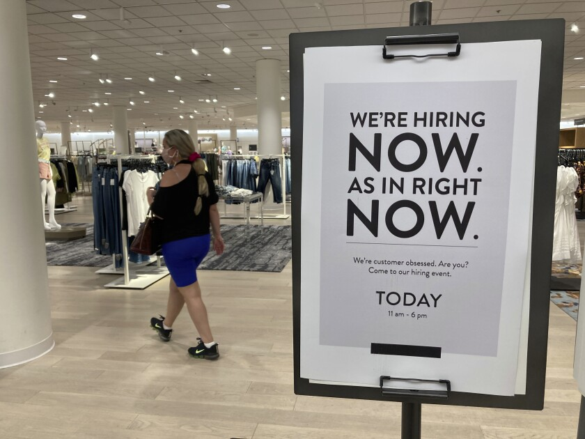 FILE - In this May 21, 2021 file photo, a customer walks behind a sign at a Nordstrom store seeking employees in Coral Gables, Fla. On Friday, Oct. 8, U.S. employers added just 194,000 jobs in September, a second straight tepid gain and evidence that the pandemic still has a grip on the economy with many companies struggling to fill millions of open jobs. (AP Photo/Marta Lavandier, File)