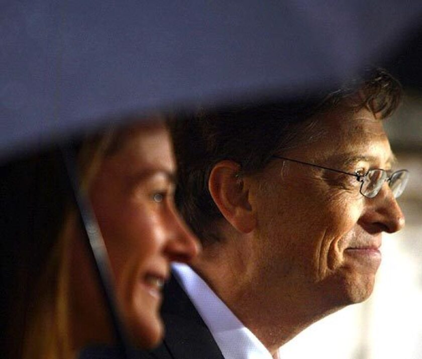 Chairman and Chief Software architect of Microsoft Bill Gates and his wife Melinda stand beneath an umbrella after he received an honorary knighthood at Buckingham Palace in London..