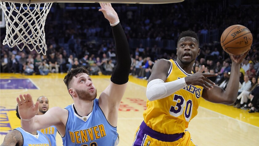 Lakers forward Julius Randle, right, shoots as Denver Nuggets center Jusuf Nurkic defends during the first half Tuesday.