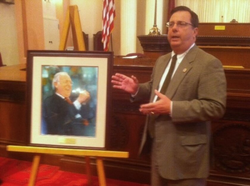 Tom Cleary, director of community and government affairs for USD, presents the portrait of the late Sen. Dave Cox.