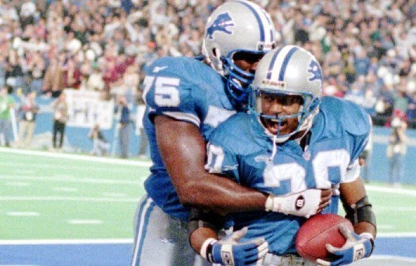 Lomas Brown hugging from behind Detroit Lions teammate Barry Sanders, holding the football, in a 1995 game.