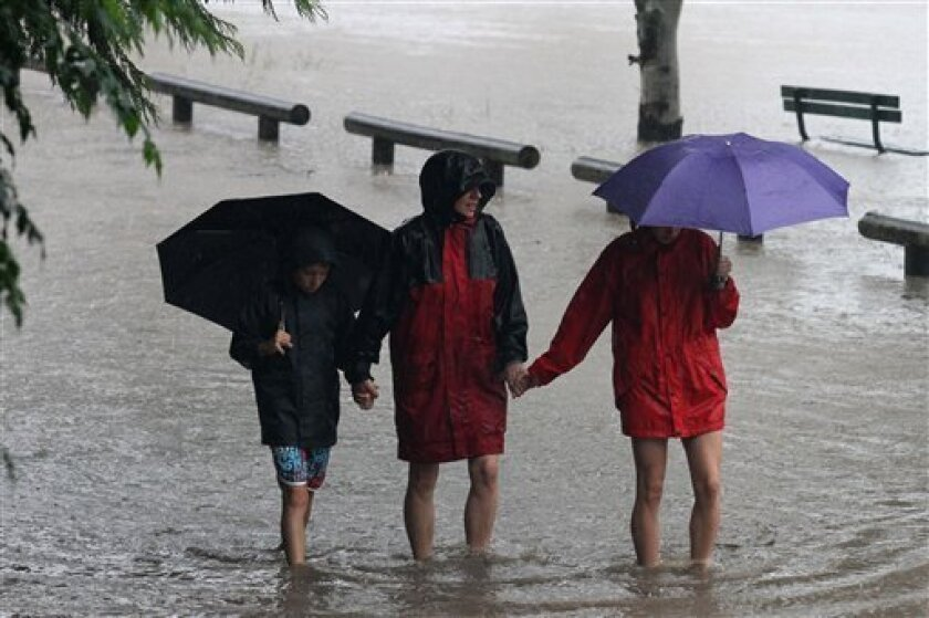 Local residents move to higher ground as the Brisbane river burst its banks to cause widespread flooding in Brisbane, Australia, on Tuesday, Jan. 11, 2011. Queensland has been in the grip of its worst flooding for more than two weeks, after tropical downpours across a vast area of the state covered an area the size of France and Germany combined. Residents in low-lying regions of the state capital of Brisbane were urged to sandbag their homes and later told to move to higher ground. (AP Photo/Tertius Pickard)