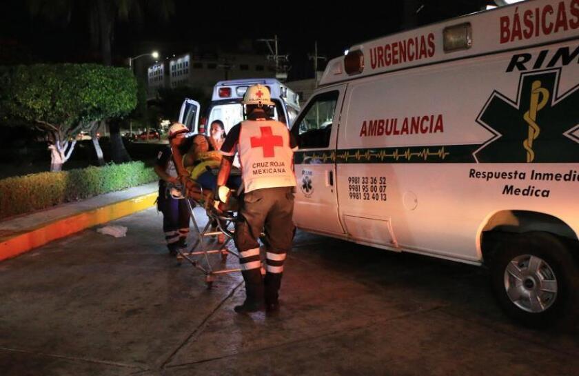 Socorristas trasladan a una paciente el miércoles hacia un hospital en Cancún (México). Un total de 230 personas resultaron intoxicadas al consumir alimentos en mal estado durante un congreso religioso en el balneario mexicano. EFE/Lourdes Cruz