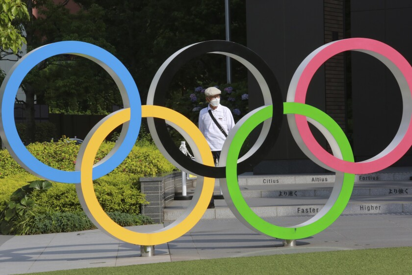 A man walks past the Olympic rings in Tokyo, Monday, June 7, 2021. (AP Photo/Koji Sasahara)