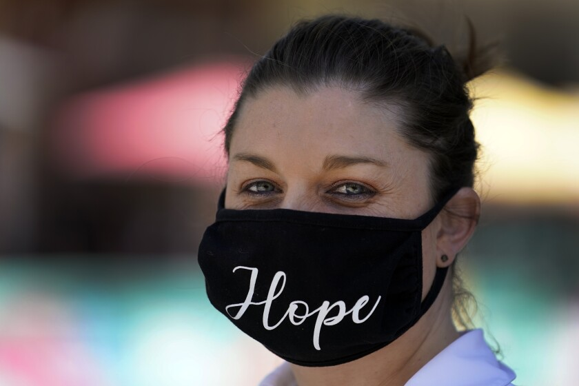 """A woman wears a mask with the word """"Hope"""" embroidered on it amid the COVID-19 pandemic Tuesday, May 18, 2021, in Burbank, Calif. (AP Photo/Marcio Jose Sanchez)"""