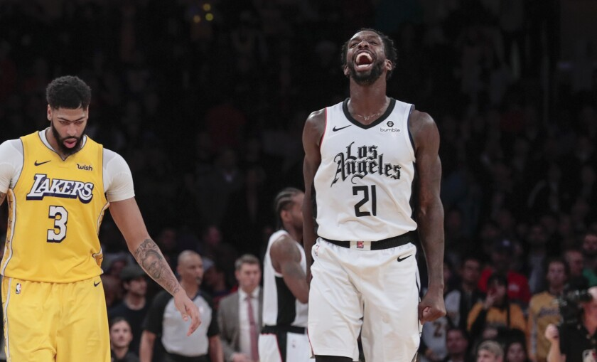 Clippers guard Patrick Beverley (21) celebrates a 111-106 win after Lakers forward Anthony Davis (3) missed an inconsequential shot at the buzzer on Dec. 25, 2019.