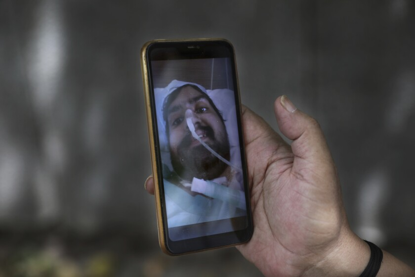 Anil Sharma shows a photograph of his son Saurav who is being treated for COVID-19 at a private hospital in New Delhi, India, Thursday, July 1, 2021. Life is tentatively returning to normal in India as coronavirus cases fall. But millions are embroiled in a nightmare of huge piles of medical bills. Most Indians don't have health insurance and costs for COVID-19 treatment have them drowning in debt. (AP Photo/Manish Swarup)