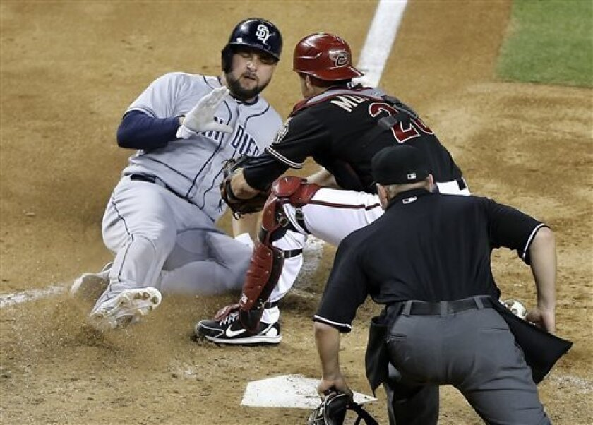 Arizona Diamondbacks catcher Miguel Montero, right, tags out San Diego Padres' Yonder Alonso at the plate during the fifth inning of a baseball game, Saturday, May 25, 2013, in Phoenix. (AP Photo/Matt York)