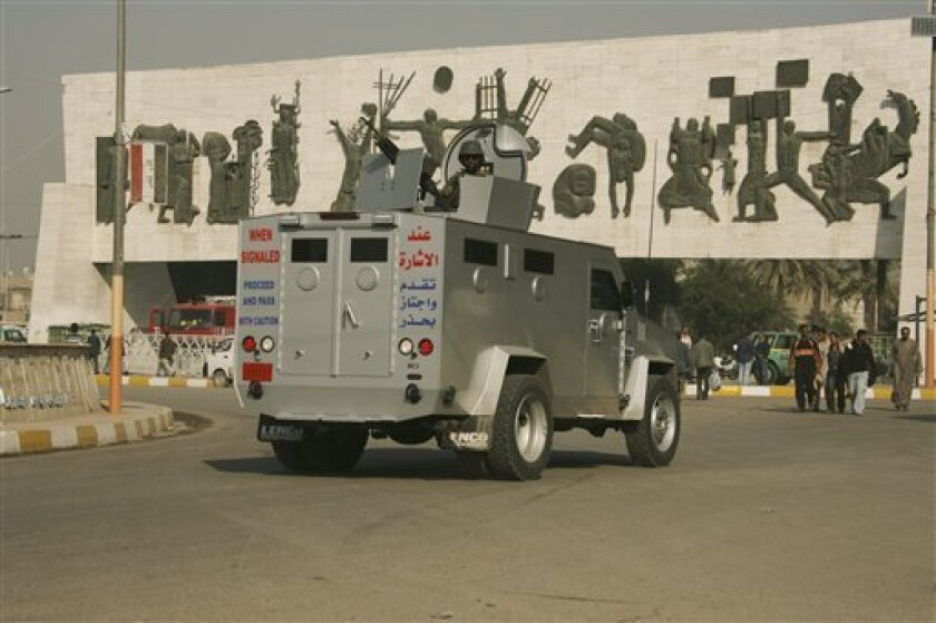 A private security company armored vehicle rolls through Tahrir square in central Baghdad, Iraq, Saturday, Dec. 13, 2008. American prosecutors met with Iraqis in Baghdad on Saturday to discuss the case against the Blackwater Worldwide guards indicted in the fatal September 2007 shooting in the city's Nisoor Square. Five Blackwater guards were indicted this week on manslaughter and other charges for their roles in the shooting that left 17 Iraqi civilians dead. (AP Photo/Hadi Mizban)