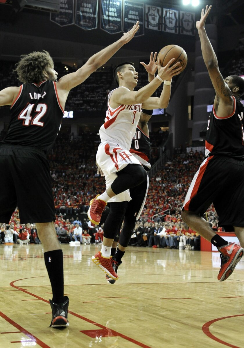 Houston Rockets' Jeremy Lin (7) goes to the basket between Portland Trail Blazers Robin Lopez (42) and LaMarcus Aldridge in the second half of Game 5 of an opening-round NBA basketball playoff series Wednesday, April 30, 2014, in Houston. The Rockets won 108-98 to send the teams back to Portland fo