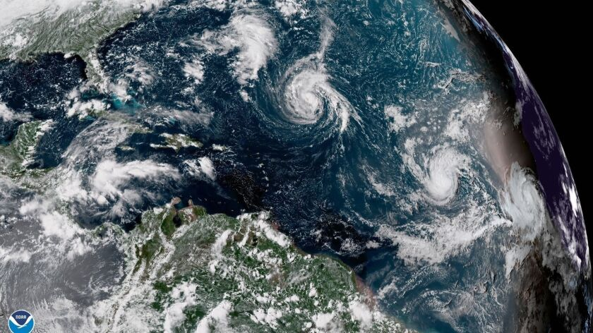 This enhanced satellite image made available by the National Oceanic and Atmospheric Administration shows Tropical Storm Florence, center, in the Atlantic Ocean on Saturday.