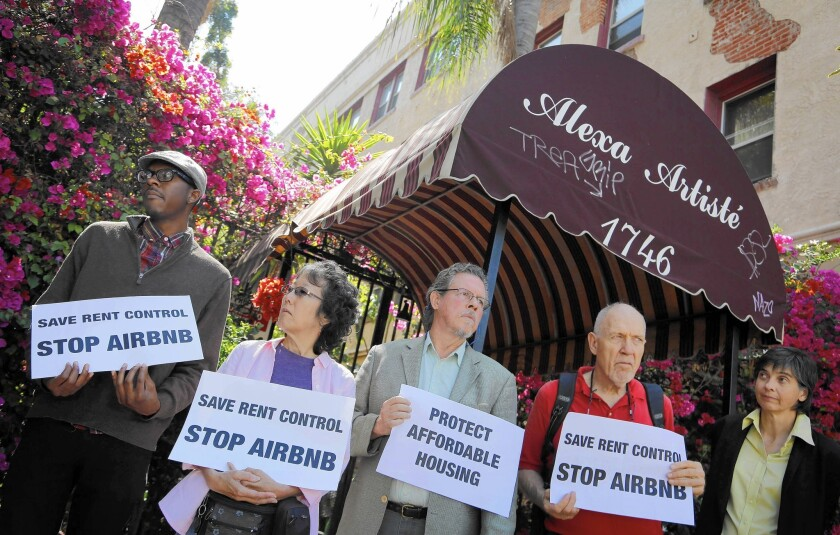 Housing and labor activists on July 15 protest outside a Hollywood apartment building that they say is being used for Airbnb rentals.
