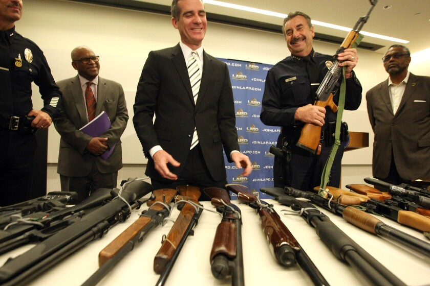 LAPD Chief Charlie Beck holds an AK-47 assault rifle standing alongside Los Angeles Mayor Eric Garcetti as they discuss the results of the city's gun buyback program.