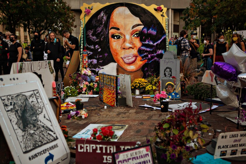 Signs and a portrait of Breonna Taylor are part of a makeshift memorial.
