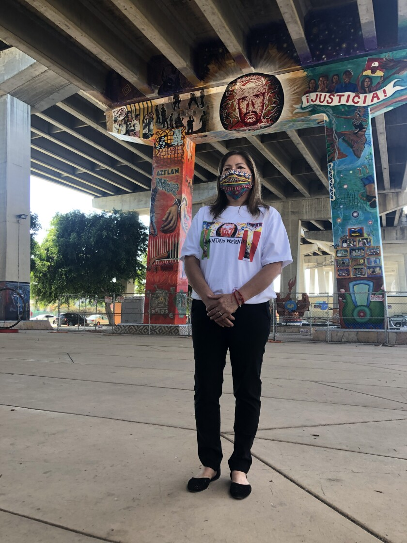 The widow of Anastasio Hernández Rojas, Maria Puga poses in front of a new mural honoring her husband.