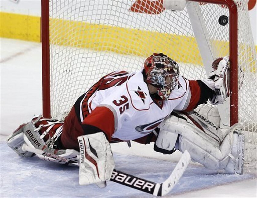 Carolina Hurricanes goaltender Justin Peters (35) cannot stop a shot from Winnipeg Jets' Paul Postma during the second period of their NHL hockey game in Winnipeg, Manitoba, Thursday, April 18, 2013. (AP Photo/The Canadian Press, John Woods)