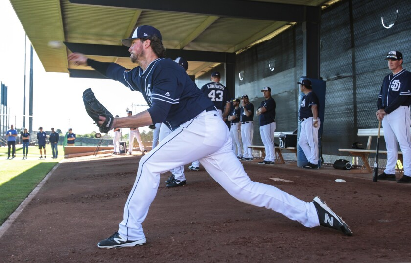 Padres pitcher Carter Capps throws in the bullpen as pitching coach Darren Balsley, far right, watches during spring training at the Peoria Sports Complex in Peoria, Arizona, on Wednesday.