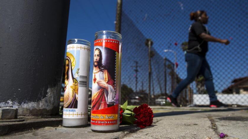 Un modesto altar para un hombre asesinado a balazos el sábado se encuentra en la intersección de la 81st y Hoover Street en el sur de Los Angeles el lunes.