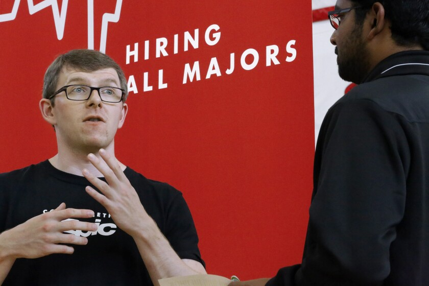 Jacob Robinson, left, of Epic, an electronic health record software company, speaks with students attending The Foot in the Door Career Fair at the University of Illinois in Springfield, Ill. Job openings were the highest in 14 years, Labor Department said.