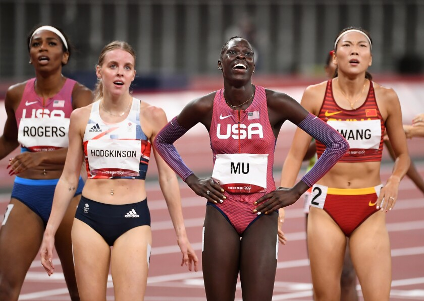 Athing Mu smiles on the track, flanked by competitors after the finish
