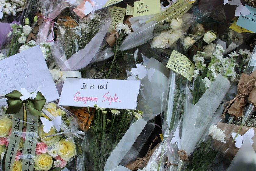 Messages left outside a subway station exit for a young woman who was slain in Seoul.