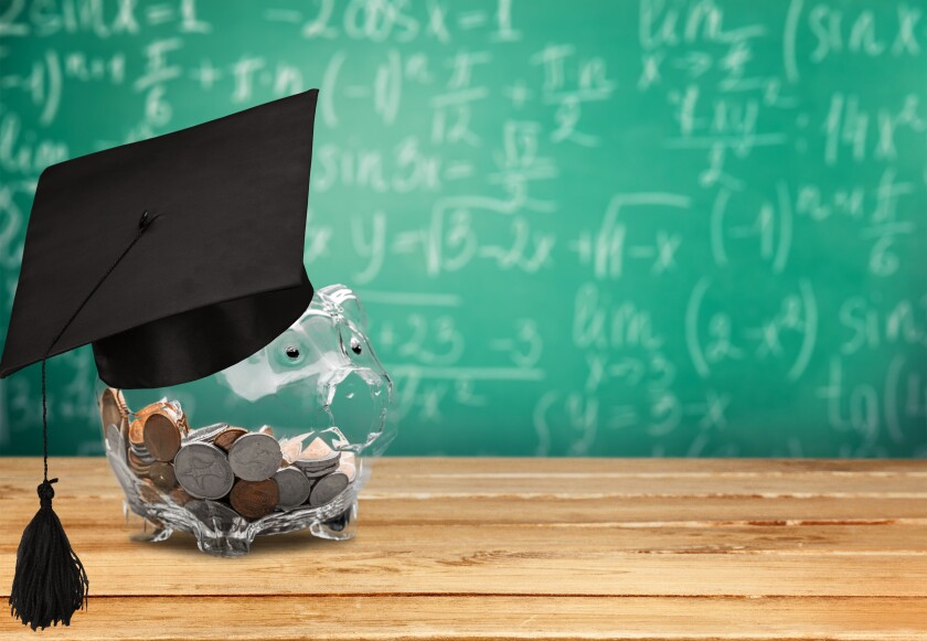 Clear piggy bank full of money with graduation cap in front of a blackboard