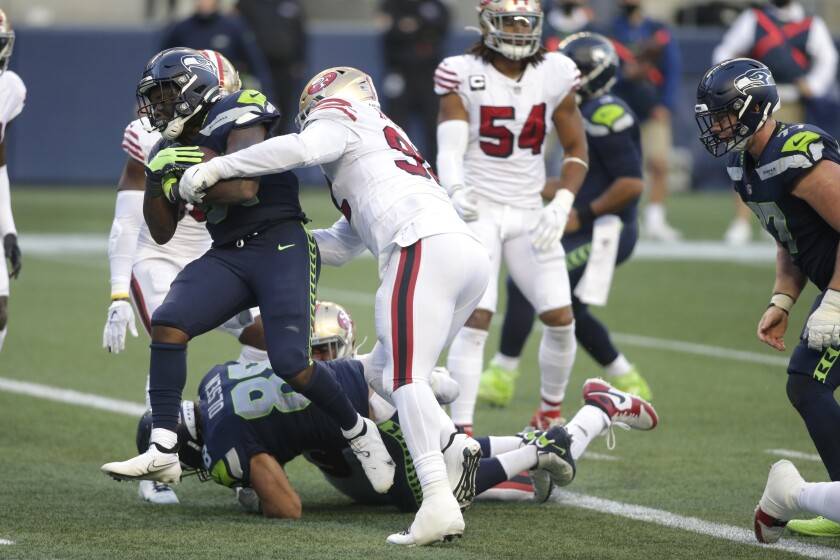 Seattle Seahawks running back DeeJay Dallas, left, scores a touchdown against the San Francisco 49ers during the second half of an NFL football game, Sunday, Nov. 1, 2020, in Seattle. The Seahawks won 37-27. (AP Photo/Scott Eklund)