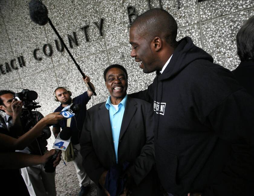 Former Long Beach high school football star Brian Banks, right, jokes with his father, Jonathan, center, outside the Long Beach courthouse after his exoneration last year.