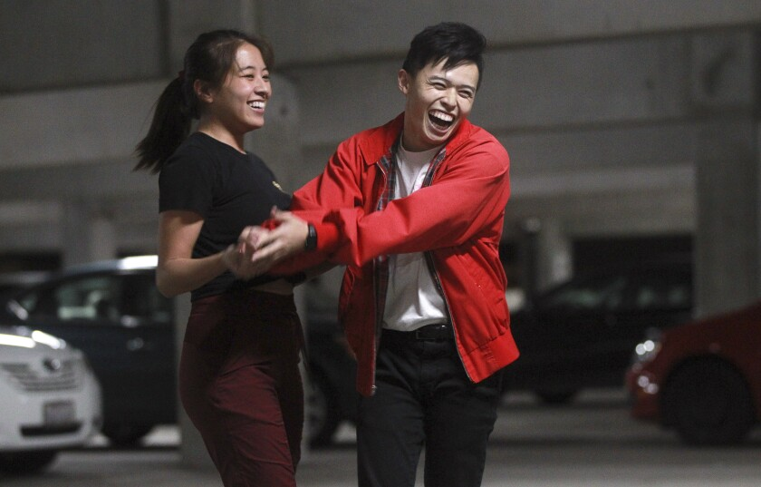 Tim Pham, and Megan Chua, both 21, smile as the crowd applauds after their dance performance during the end of the year choreography project put on by the SDSU Vietnamese Student Organization Modern, a collegiate hip-hop dance troupe, in a parking garage on the SDSU campus on Thursday, December 5, 2019 in San Diego, California.