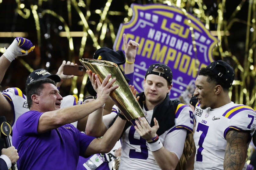 LSU head coach Ed Orgeron on the left and quarterback Joe Burrow in the center hold the trophy alongside deep Grant Delpit after the college football game against Clemson on Monday in New Orleans . LSU won 42-25.