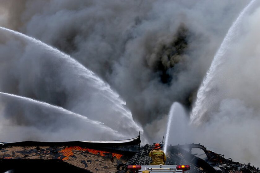 Smoke billows from an abandoned food processing plant in industry, where firefighters battled a three-alarm fire blaze.