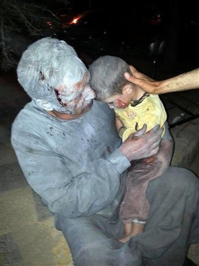 This citizen journalism image taken on Thursday, April 25, 2013 and provided by Edlib News Network, ENN, which has been authenticated based on its contents and other AP reporting, shows a wounded Syrian man holding his injured son after an air raid on the northwestern town of Saraqeb in the provinc