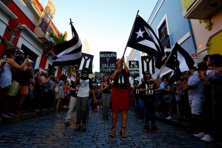 """El grupo llamado: """"Se acabaron las promesas"""", se une a miles de personas que celebran las Fiestas de la Calle San Sebastián, con la tradicional comparsa a ritmo de plena, en San Juan (Puerto Rico). EFE"""
