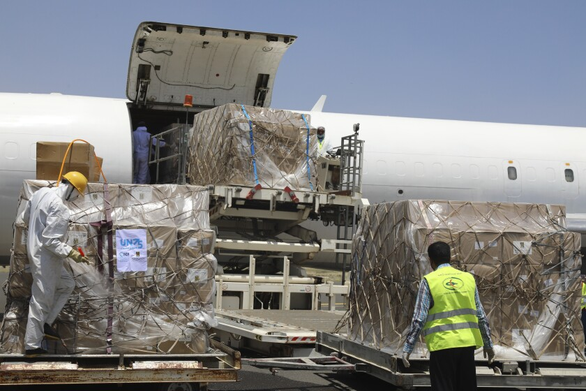 In this Wednesday, June 17, 2020, workers unload boxes of medical supplies on arrival at Sanaa International Airport in Sanaa, Yemen. The shipment includes ventilators, coronavirus test kits, PCR machines and personal protective equipment. Organized by the United Nations and private companies, it comes as the UN is facing a funding shortage for its operations in the war-torn country, where officials and medical experts fear the coronavirus could be spreading unchecked due to limited medical facilities. (World Health Organization via AP)
