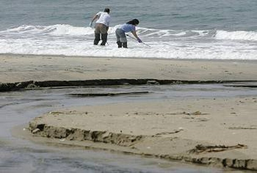 Where Cottonwood Creek flows into the ocean at Moonlight Beach in Encinitas, environmental specialists Mayela Padilla (right) and Ewan Moffat take water samples from the ocean 25 yards south of where the creek flows. They also took samples 25 yards north.